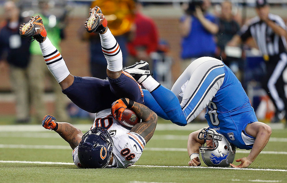 Description of . Chicago Bears defensive end Julius Peppers (90) recovers a loose ball and is stopped by Detroit Lions quarterback Matthew Stafford (9) during the second quarter of an NFL football game at Ford Field in Detroit, Sunday, Dec. 30, 2012. (AP Photo/Rick Osentoski)