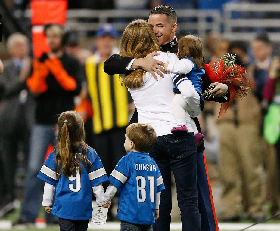 """. As part of the team\'s annual \""""Salute to Service\"""" game, the Detroit Lions welcomed Michigan native, Marine Captain Josh Munsee and his family for a surprise on-field homecoming between the first and second quarter of the game against the Tampa Bay Buccaneers at Ford Field on November 24, 2013 in Detroit, Michigan. (Photo by Gregory Shamus/Getty Images)"""