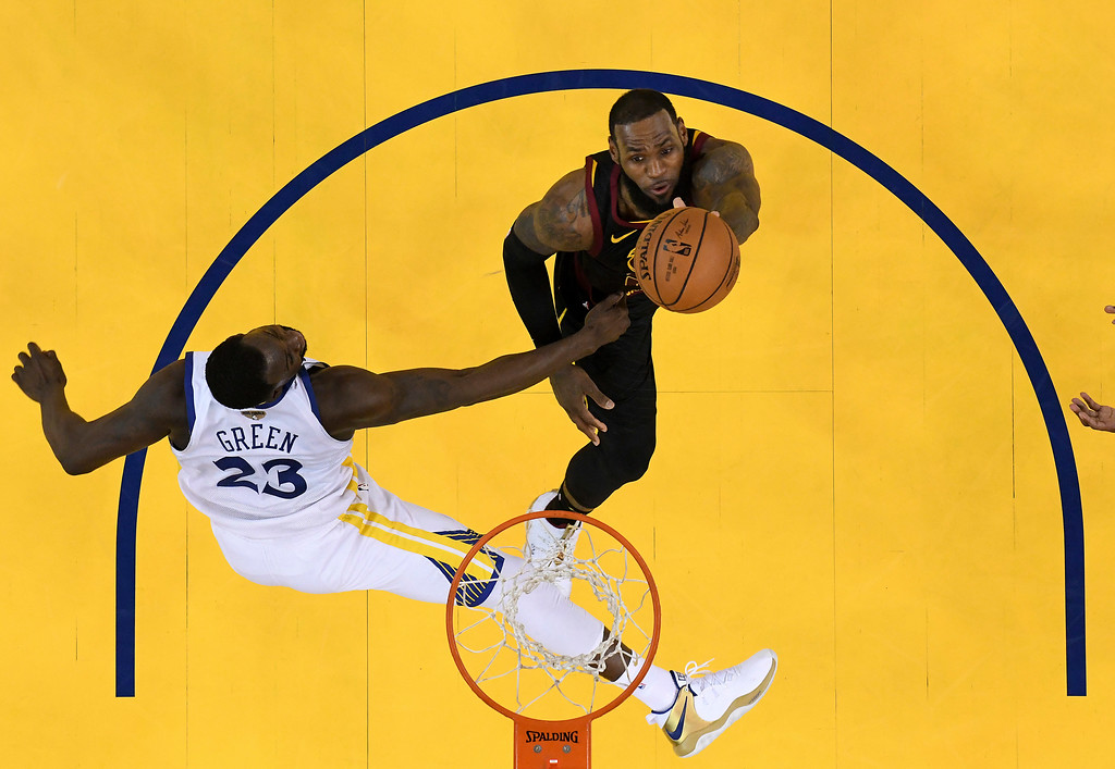 . Cleveland Cavaliers forward LeBron James, top, shoots against Golden State Warriors forward Draymond Green during the second half of Game 1 of basketball\'s NBA Finals in Oakland, Calif., Thursday, May 31, 2018. The Warriors won 124-114 in overtime. (Kyle Terada/Pool Photo via AP)