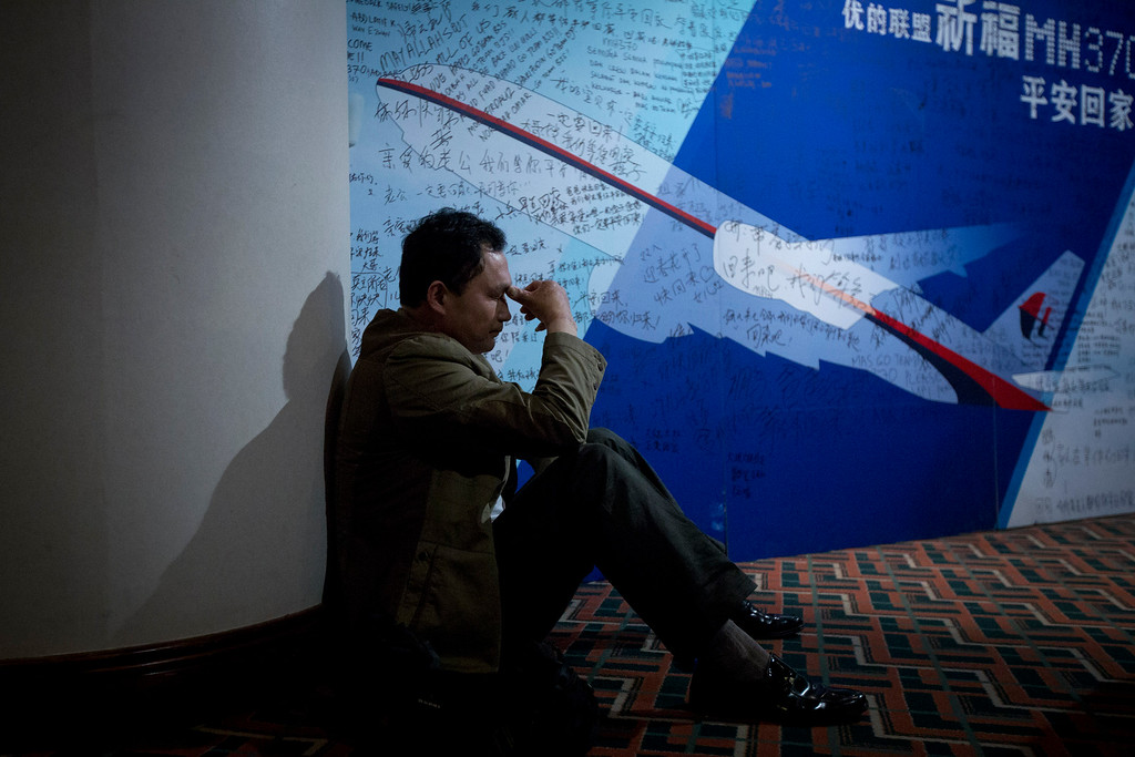 """. A man, one of the relatives of Chinese passengers onboard Malaysia Airlines Flight 370, rests near a board covered with written wishes at a hotel in Beijing, China, Saturday, March 29, 2014. Some of the wishes are \""""Dear husband, you must stay strong, I am waiting for you. Dear father, please be back  home safely and the whole family is here waiting for you.\"""" (AP Photo/Alexander F. Yuan)"""