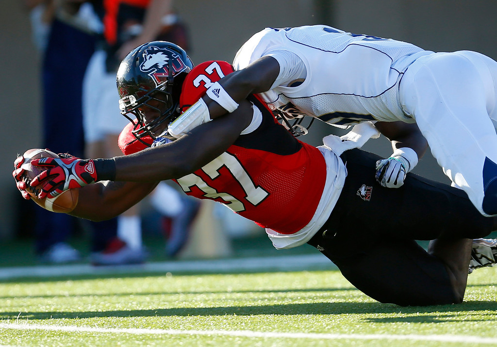 . Northern Illinois tight end Desroy Maxwell (37) stretches the ball over the goal line for a touchdown as Akron cornerback Emmanuel Lartey, right, tries to make the tackle during the first half of an NCAA college football game on Saturday, Oct. 12 , 2013, in DeKalb, Ill. (AP Photo/Jeff Haynes)