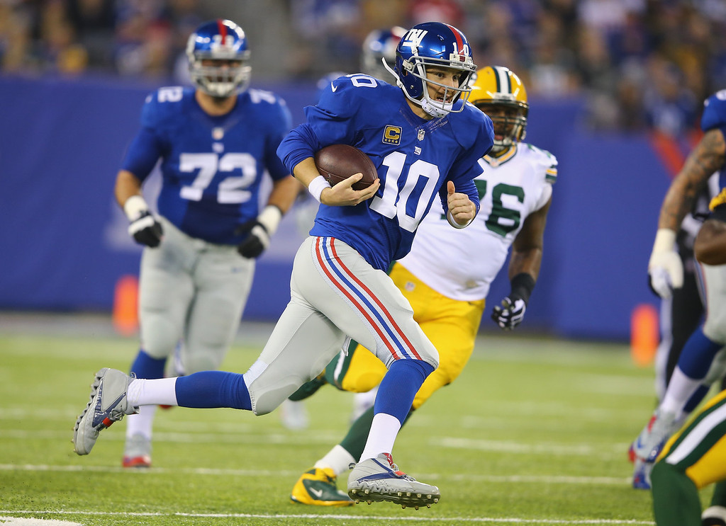 . Eli Manning #10 of the New York Giants scrambles against the Green Bay Packers during their game at MetLife Stadium on November 17, 2013 in East Rutherford, New Jersey.  (Photo by Al Bello/Getty Images)