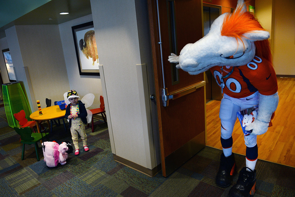 . Miles, the Broncos Mascot , tries to coax 3 year old Raya Smith to come say hello to him in the waiting room of Rocky Mountain Hospital for Children in Denver, Co on January 14, 2014.   (Photo By Helen H. Richardson/ The Denver Post)