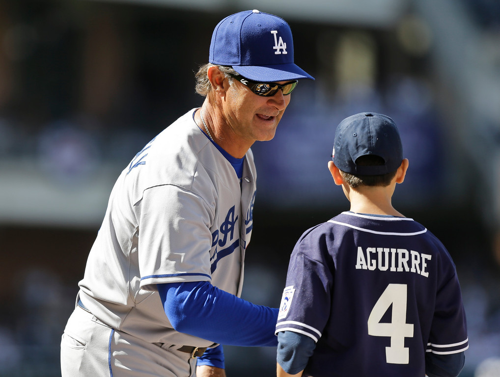 . Los Angeles Dodgers manager Don Mattingly greets a Little League player during team introductions at the home opener baseball game for the San Diego Padres in San Diego, Tuesday, April 9, 2013. (AP Photo/Lenny Ignelzi)