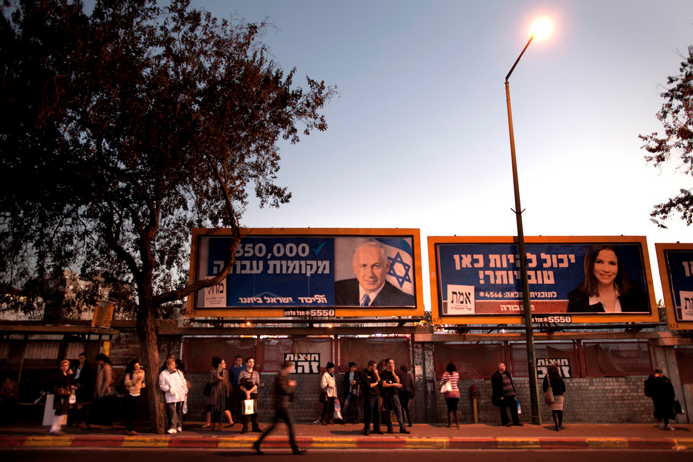 Description of . Israelis wait for transportation under election campaign billboards of Israeli Prime Minister and Likud Party leader Benjamin Netanyahu, left, and Israel's Labor party candidate Shelly Yachimovich, in the central Israeli city of Ramat Gan, Monday, Jan. 21, 2013. The general elections will be held on Tuesday, Jan. 22, 2013. Hebrew on the billboard at right reads,