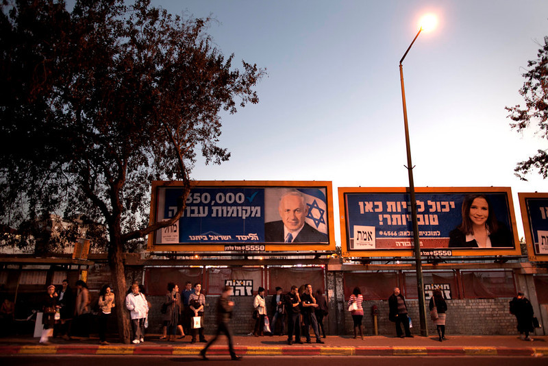 """. Israelis wait for transportation under election campaign billboards of Israeli Prime Minister and Likud Party leader Benjamin Netanyahu, left, and Israel\'s Labor party candidate Shelly Yachimovich, in the central Israeli city of Ramat Gan, Monday, Jan. 21, 2013. The general elections will be held on Tuesday, Jan. 22, 2013. Hebrew on the billboard at right reads, \"""" It can be better here,\"""". and at left, \""""350,000 job positions.\"""" (AP Photo/Oded Balilty)"""