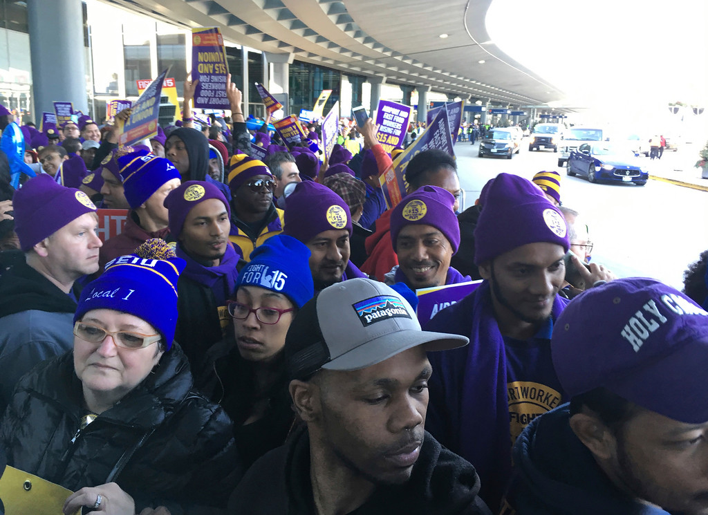 . Protesters calling for a $15 per hour minimum wage march outside terminals at O\'Hare International Airport, Tuesday, Nov. 29, 2016, in Chicago. Police gated an area to allow travelers room to walk. (AP Photo/Kiichiro Sato)