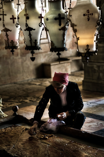 Pilgrim praying at the exact spot where Jesus is believed to have been laid after being taken down from the cross.  Church of the Holy Sepulchre in Jerusalem, Israel, 2012.