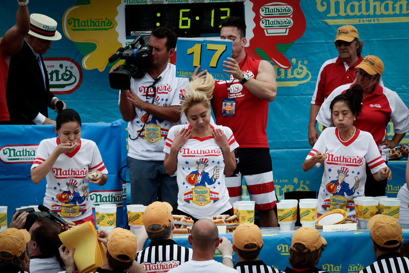 . (L-R) Sonya Thomas, Miki Sudo and Juliet Lee compete in the women\'s division of the Nathan\'s Famous Hot Dog Eating Contest at Coney Island on July 4, 2014 in the Brooklyn borough of New York City.  Sudo beat reigning champion Sonya Thomas by eating 34 hot dogs in 10 minutes. Joey Chesnut won his eighth straight Nathan\'s Hot Dog Eating Contest with 61 hot dogs. (Photo by Kena Betancur/Getty Images)