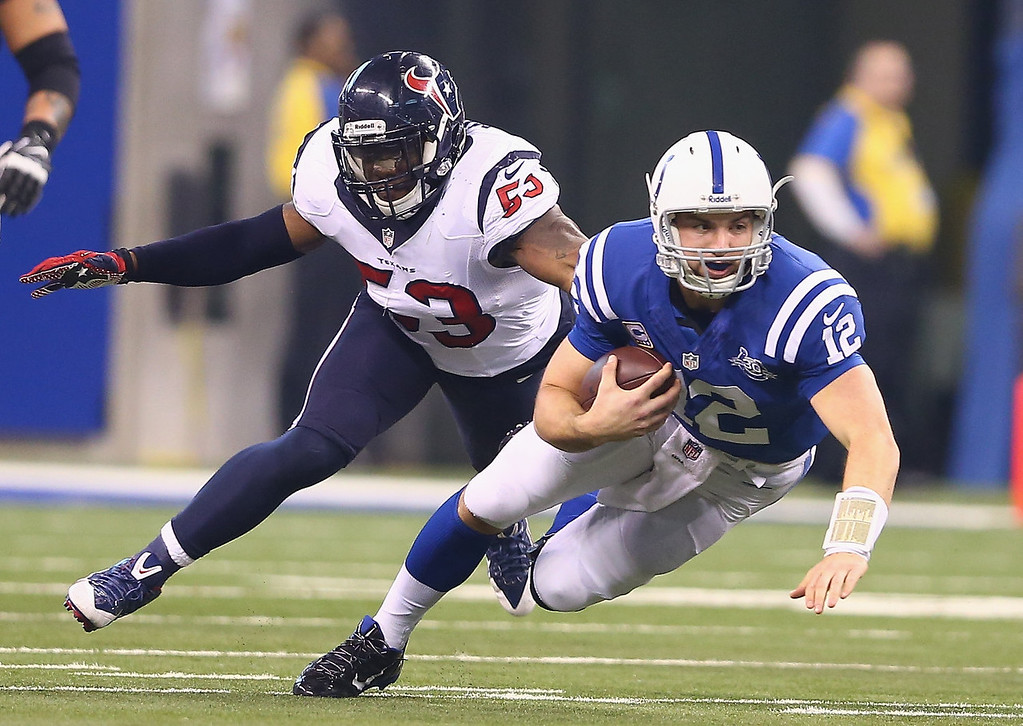 . Andrew Luck #12 of the Indianapolis Colts runs with the ball while defended by Joe Mays #53 of the Houston Texans during the NFL game at Lucas Oil Stadium on December 15, 2013 in Indianapolis, Indiana.  (Photo by Andy Lyons/Getty Images)