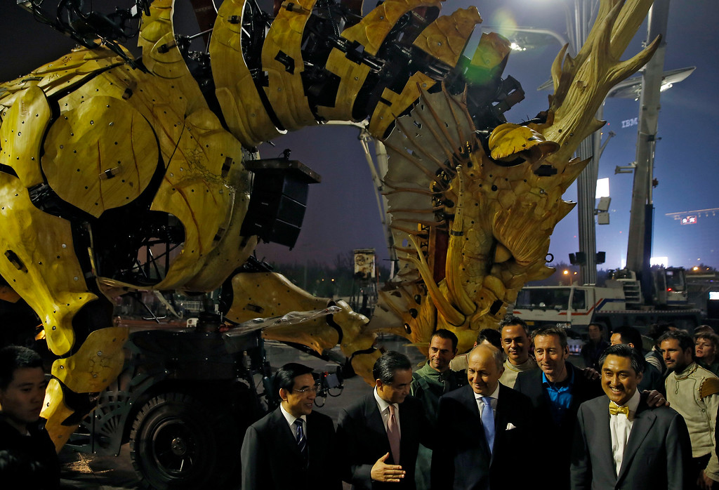 """. French Foreign Minister Laurent Fabius, foreground second right, and his Chinese counterpart Wang Yi, second left, stand in front of the French production company La Machine\'s latest creation \""""the Long Ma\"""" or Dragon Horse after a performance held in front of the Bird\'s Nest Stadium in Beijing, China Sunday, Oct. 19, 2014. The performance, which attended by Laurent Fabius and Wang Yi, mark the climax of celebrations for the 50th anniversary of Sino-French diplomatic relations. (AP Photo/Andy Wong)"""