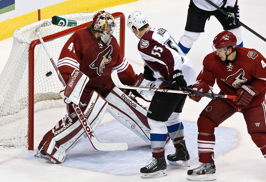 . Phoenix Coyotes\' Mike Smith, left, gives up a goal to Colorado Avalanche\'s P.A. Parenteau as the Avalanches\' Cody McLeod (55) and Coyotes\' Zbynek Michalek (4), of the Czech Republic, both look on during the first period in an NHL hockey game, on Friday, April 26, 2013, in Glendale, Ariz. (AP Photo/Ross D. Franklin)