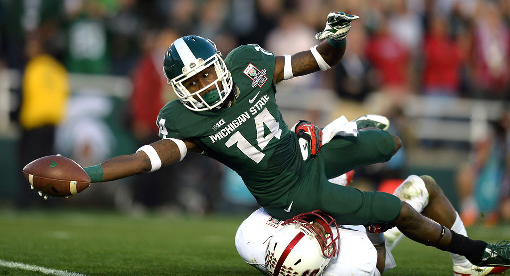 . Michigan State Tony Lippett dives in for a fourth-quarter  touchdown on a 25-yard pass play as Stanford\'s Wayne Lyons defends at the Rose Bowl, Wednesday, January 1, 2014. (Photo by Michael Owen Baker/L.A. Daily News)