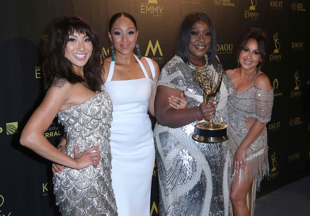 ". Jeannie Mai, from left, Tamera Mowry-Housley, Loni Love and Adrienne Houghton pose in the press room with the award for outstanding entertainment talk show host for ""The Real\"" at the 45th annual Daytime Emmy Awards at the Pasadena Civic Center on Sunday, April 29, 2018, in Pasadena, Calif. (Photo by Willy Sanjuan/Invision/AP)"
