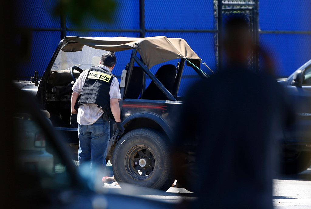 . A crime scene investigator looks inside the off-road vehicle where they found a male body in the tennis court parking lot at San Jose State University in San Jose, Calif., on Sunday, Sept. 8, 2013.  Both the San Jose Police and San Jose State University agencies responded to the scene. (Josie Lepe/Bay Area News Group)