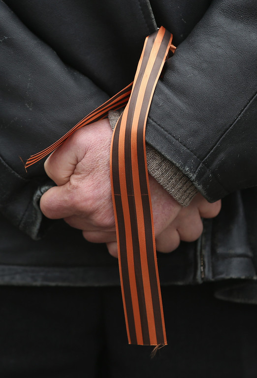 . A man wears the Ribbon of St. George, a symbol of Russian military valor, at a gathering of pro-Russian supporters outside the Crimean parliament building on February 28, 2014 in Simferopol, Ukraine. According to media reports Russian soldiers have occupied the airport at nearby Sevastapol while soldiers whose identity could not be initially confirmed have stationed themselves at Simferopol International Airport in moves that are raising tensions between Russia and the new Kiev government. Crimea has a majority Russian population and armed, pro-Russian groups have occupied government buildings in Simferopol.  (Photo by Sean Gallup/Getty Images)