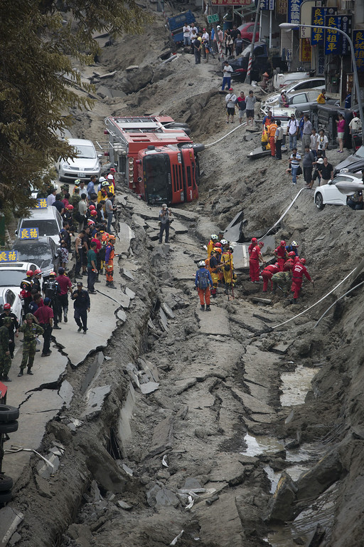 . Rescue workers search through the site of the damaged road after several gas explosions in southern Kaohsiung on August 1, 2014 in Kaohsiung, Taiwan. A series of powerful gas blasts killed 25 people and injured up to 267 in the southern Taiwanese city of Kaohsiung, overturning cars and ripping up roads, officials said.  (Photo by Ashley Pon/Getty Images)