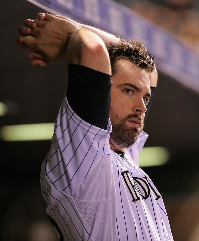 . DENVER, CO - AUGUST 05:  Boone Logan #48 of the Colorado Rockies looks on from the dugout as he collected the loss as he Chicago Cubs defeated the Rockies 6-5 in 12 innings at Coors Field on August 5, 2014 in Denver, Colorado.  (Photo by Doug Pensinger/Getty Images)