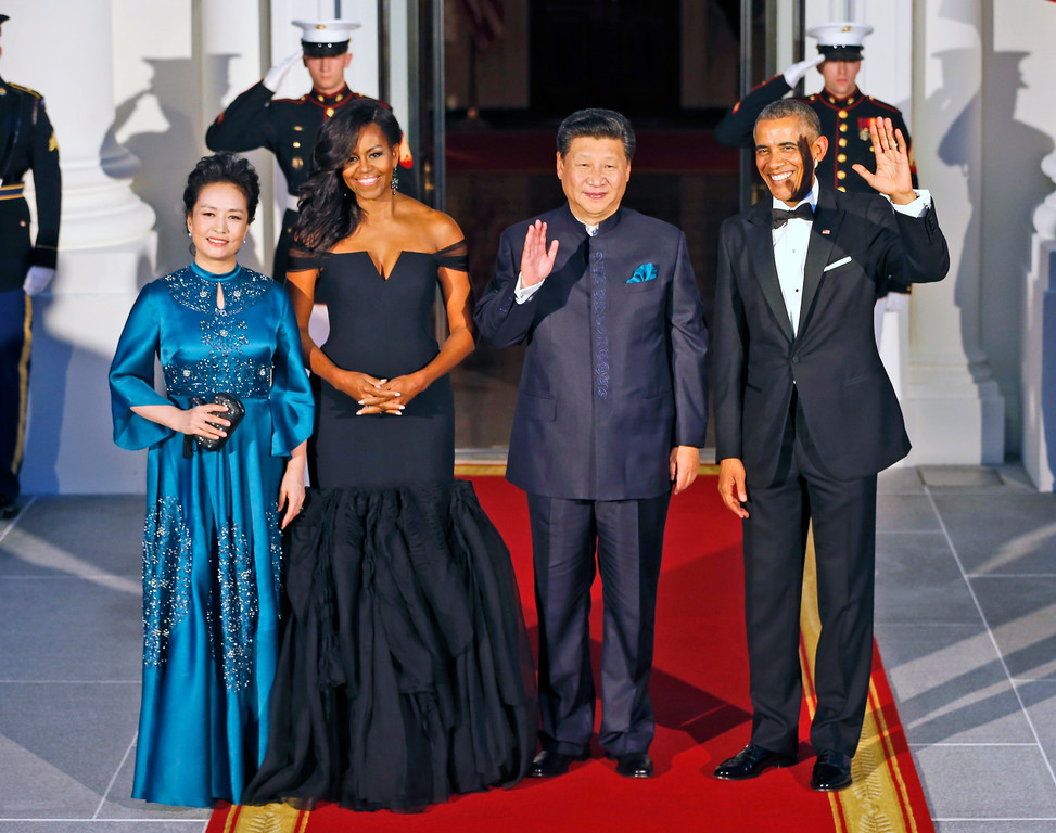 . President Barack Obama, right, and Chinese President Xi Jinping, second from right, wave on the North Portico with wives Peng Liyuan, left, and first lady Michelle Obama as they arrive for a State Dinner at the White House in Washington, Friday, Sept. 25, 2015. (AP Photo/Steve Helber)