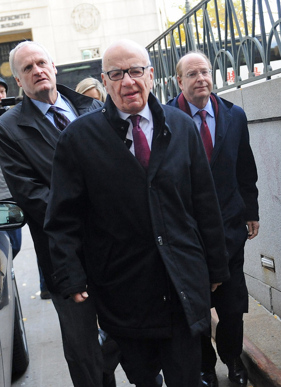 . Rupert Murdoch, center, arrives at State Supreme court, Wednesday, Nov. 20, 2013, in New York.  (AP Photo/ Louis Lanzano)