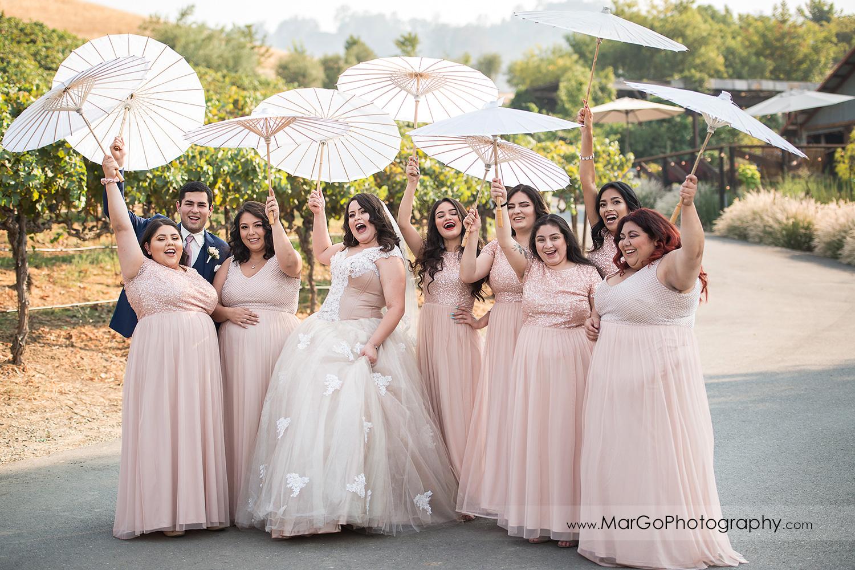 bride and bridesmaids waving white umbrellas at Taber Ranch Vineyards