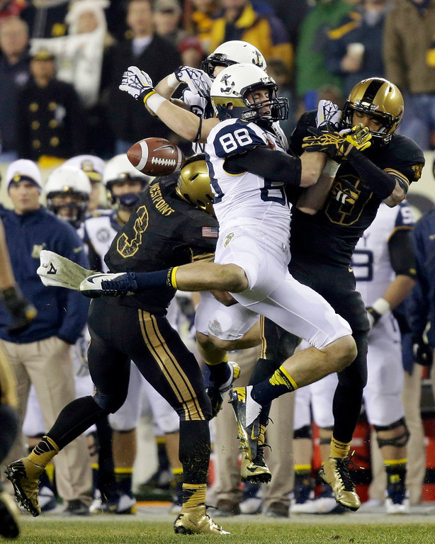 . Army\'s Chris Carnegie, left, and Brandon Fusilier-Jeffires, right, collide with Navy\'s Casey Bolena, second from right, and Matt Aiken on an incomplete pass during the second half of an NCAA college football game, Saturday, Dec. 8, 2012, in Philadelphia. Navy won 17-13. (AP Photo/Matt Slocum)