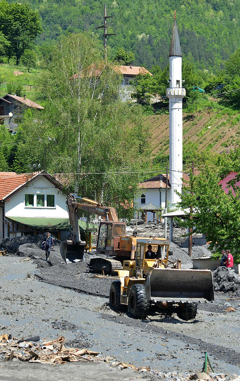 . Workers use a backhoe and a bulldozer to clear the earth after a landslide in the flooded village of Topcic Polje, near the northern Bosnian city of Doboj, on May 19, 2014, after the river Bosna flooded entire agricultural fields and several urban areas along its flow during the weekend\'s rainfall, which also caused landslides. Thousands crammed into boats and army trucks as they fled their homes in Serbia and Bosnia on MAy 18 after record rainfalls. Officials say the disaster has killed at least 44 people so far.  AFP PHOTO / ELVIS BARUKCIC/AFP/Getty Images