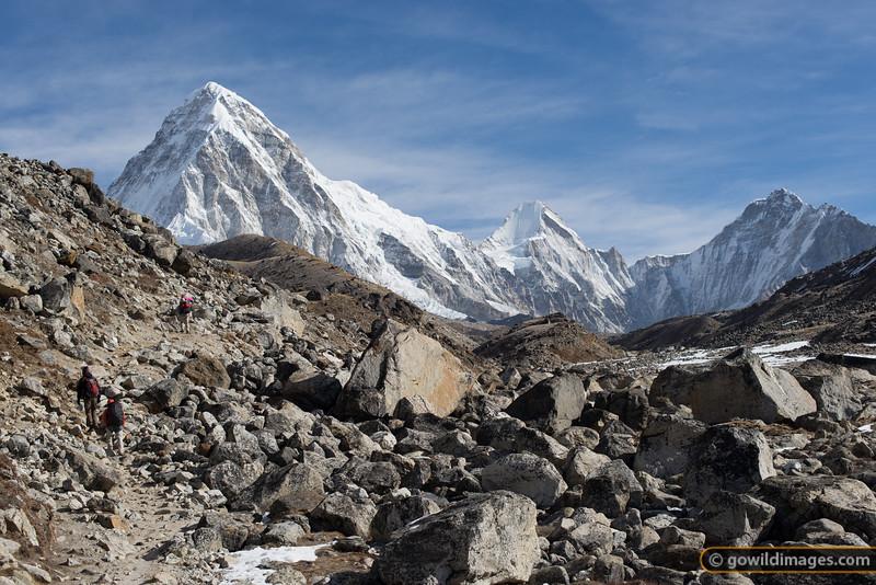 Porter, trekker and guide on the trail to EBC. Mountains L-R: Pumori, Lingtren, Khumbutse.