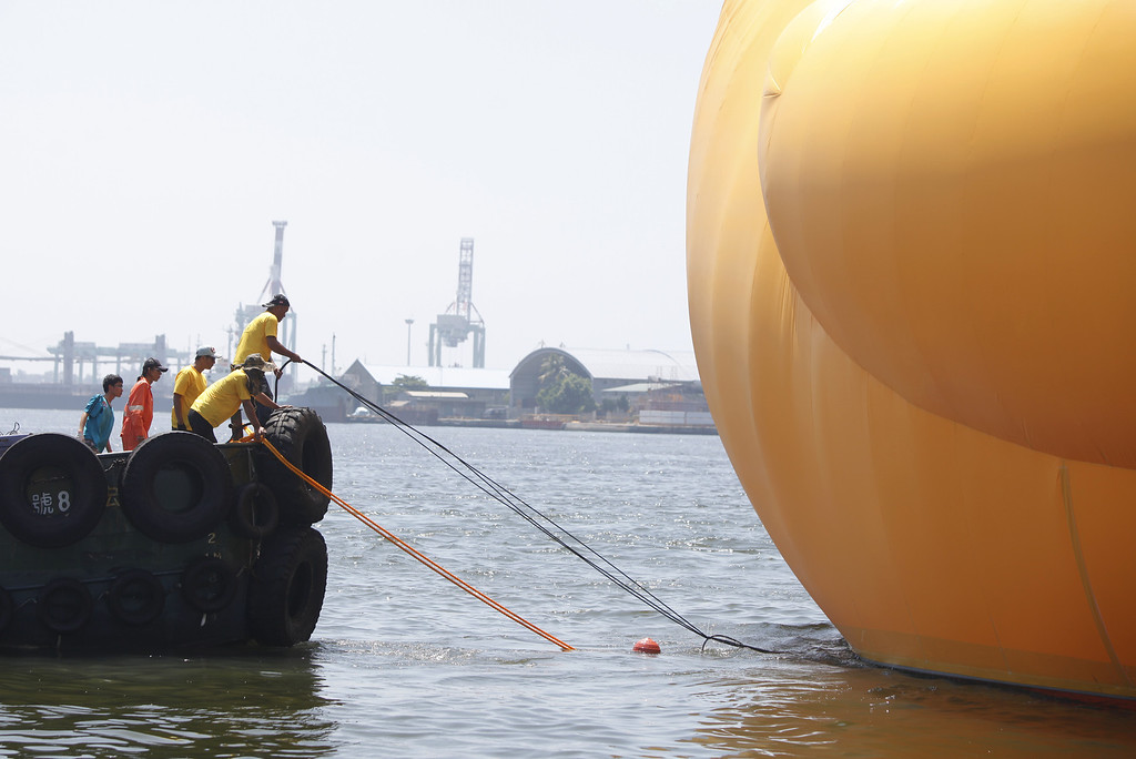 . A giant Rubber Duck by Dutch conceptual artist Florentijin Hofman is pulled into Glory Pier on September 19, 2013 in Kaohsiung, Taiwan. The \'Rubber\' Duck,\' is traveling the world and will stop in Kaohsiung from September 19 to October 20.  (Photo by Ashley Pon/Getty Images)