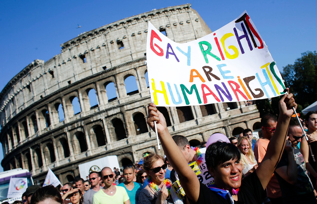 . A woman holds her banner in front of the Colosseum during the annual gay pride parade in downtown Rome June 15, 2013. REUTERS/Max Rossi