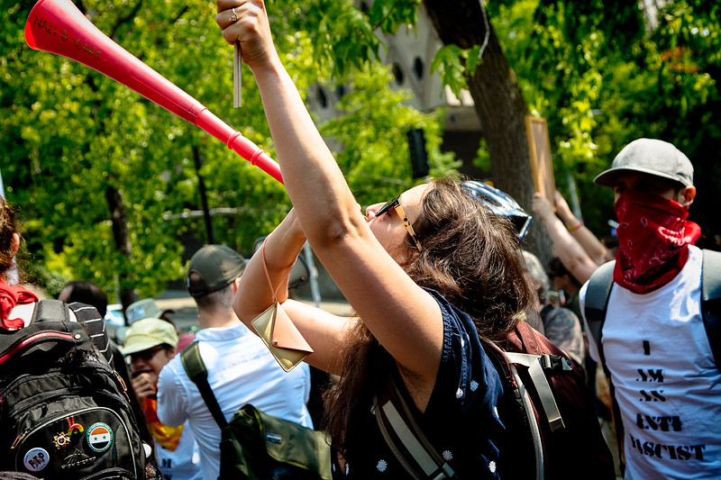 A left wing demonstrator holds a protest sign and blows on a vuvuzela at the right wing gathering across the street at Seattle City Hall.