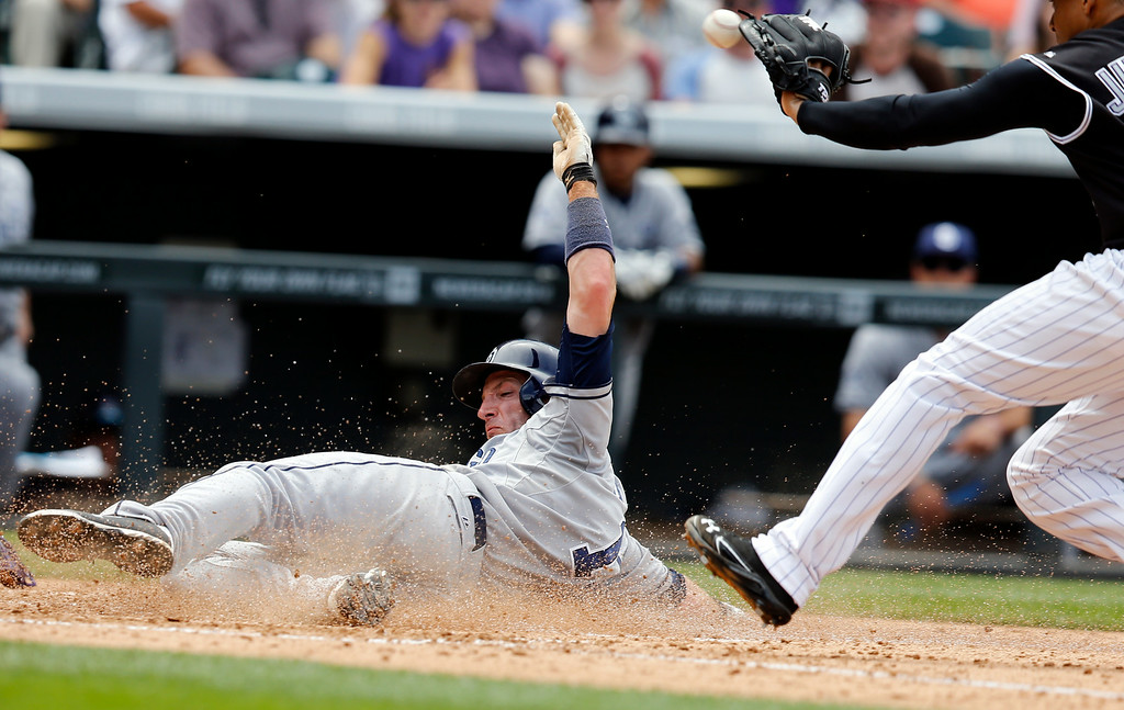 . San Diego Padres\' Chris Denorfia scores on a Colorado Rockies starting pitcher Jair Jurrjens wild pitch during the fifth inning of a baseball game on Wednesday, July 9, 2014, in Denver. (AP Photo/Jack Dempsey)