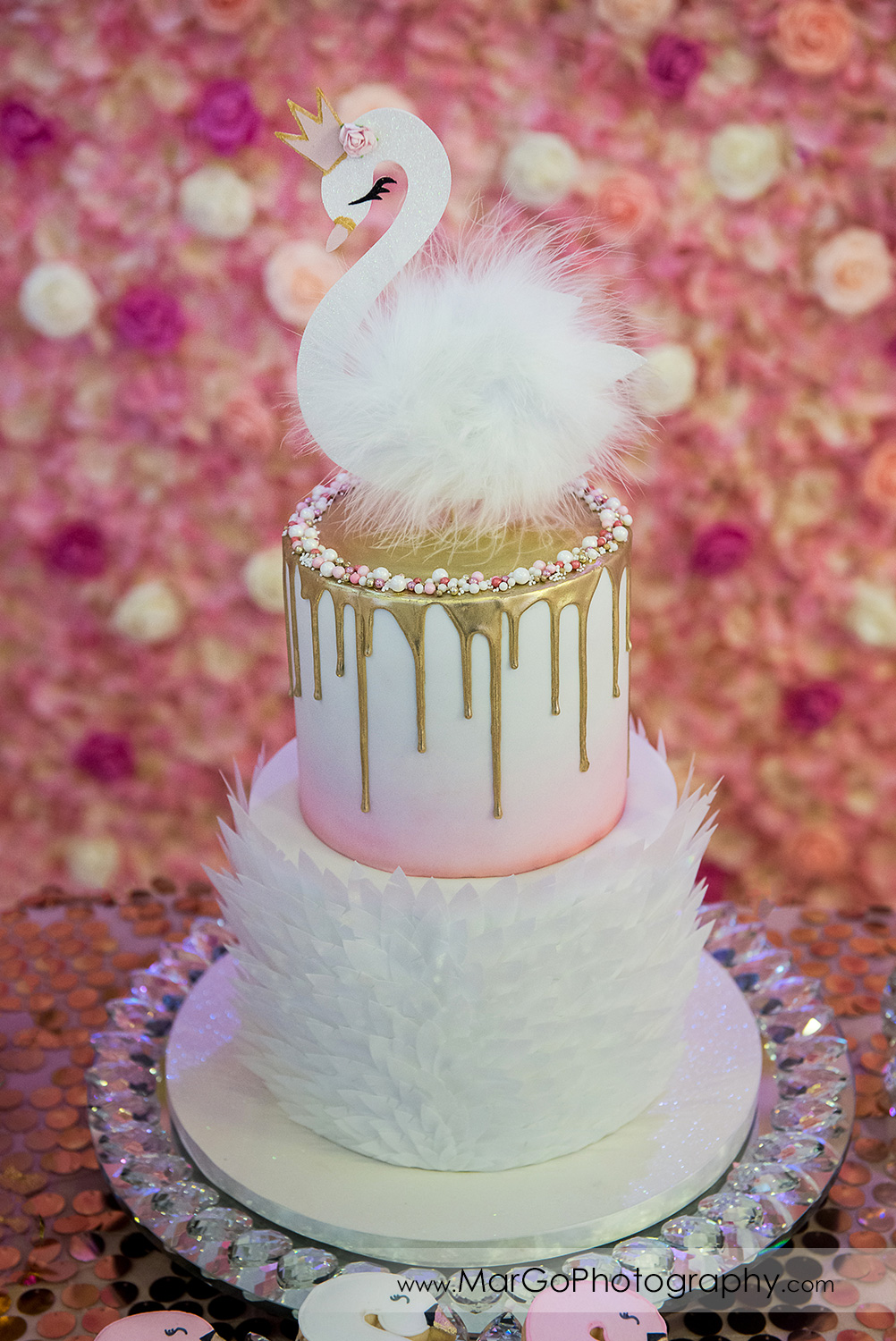 white, pink and gold cake with swan topper at Newark Oasis Palace