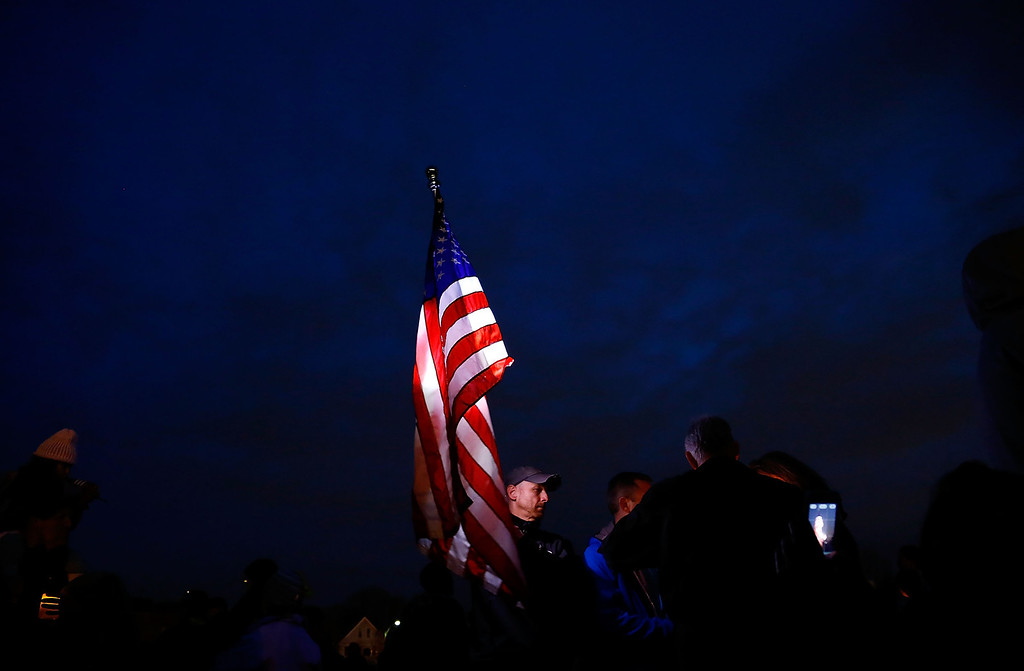 . BOSTON, MA - APRIL 16: A man carries a large American flag during a vigil for eight-year-old Martin Richard, from Dorchester, who was killed by an explosion near the finish line of the Boston Marathon on April 16, 2013 at Garvey Park in Boston, Massachusetts. The twin bombings resulted in the deaths of three people and hospitalized at least 128. The bombings at the 116-year-old Boston race resulted in heightened security across the nation with cancellations of many professional sporting events as authorities search for a motive to the violence. (Photo by Jared Wickerham/Getty Images)