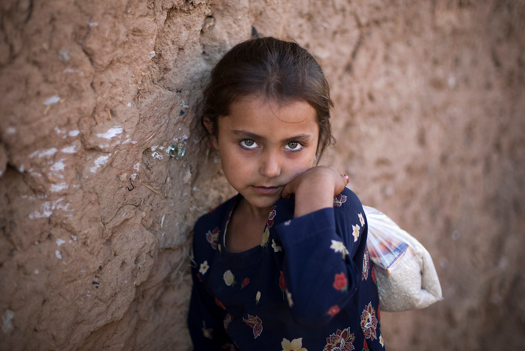 . Ameena Bibi, who is displaced from Pakistani tribal area due to security forces\' crackdown against militants, stands outside her mudnhouse living under a poverty line in suburbs of Islamabad, Pakistan, Friday, Oct 17, 2014. (AP Photo/B.K. Bangash)