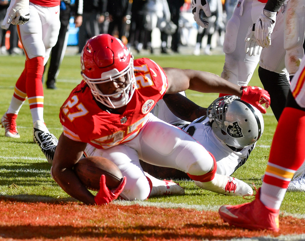 . Kansas City Chiefs running back Kareem Hunt (27) scores on a one-yard run in front of Oakland Raiders linebacker NaVorro Bowman (53), during the first half of an NFL football game in Kansas City, Mo., Sunday, Dec. 10, 2017. (AP Photo/Ed Zurga)
