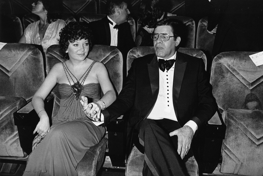 """. American actor-comedian Jerry Lewis, right, and his new wife, Sam, hold hands in a screening room at the Cannes Film Festival in Cannes, France, May 7, 1983.  Lewis stars as a talk-show host in the movie \""""The King of Comedy,\"""" presented at the Festival.  (AP Photo/J. Langevin)"""