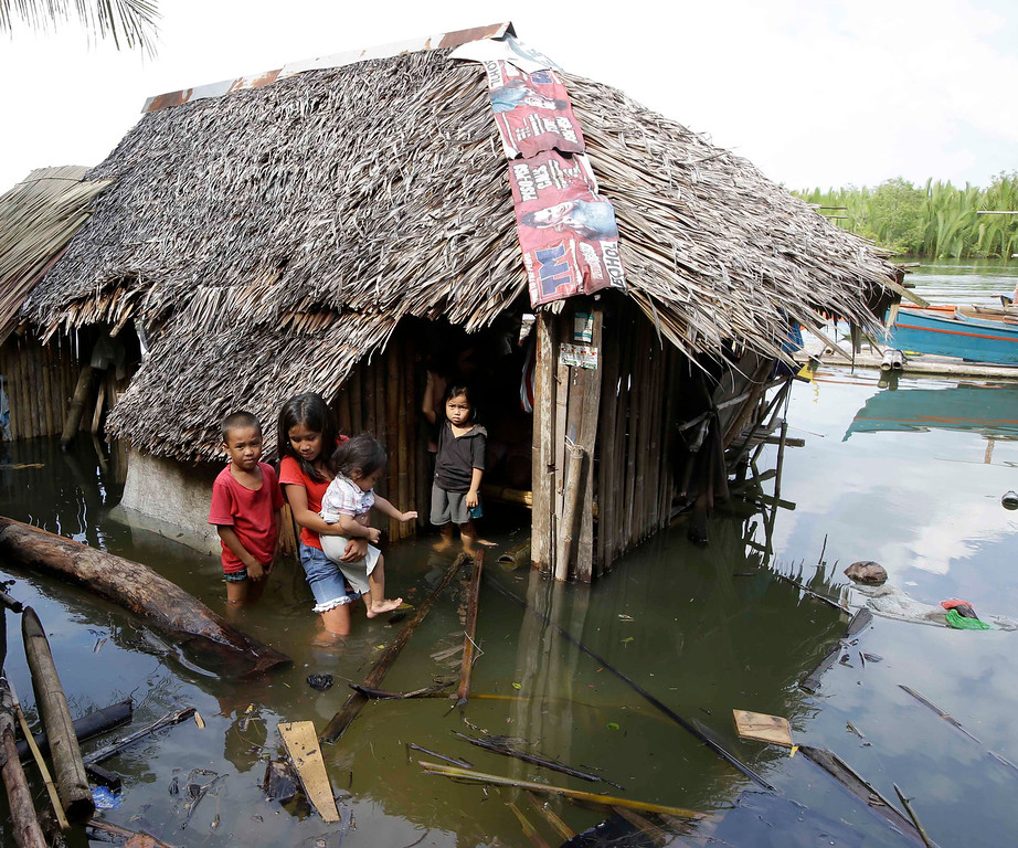 . Children emerge from their half-submerged home which was damaged by Tuesday\'s 7.2-magnitude earthquake in Cortes township, Bohol province in central Philippines Wednesday, Oct. 16, 2013.   (AP Photo/Bullit Marquez)