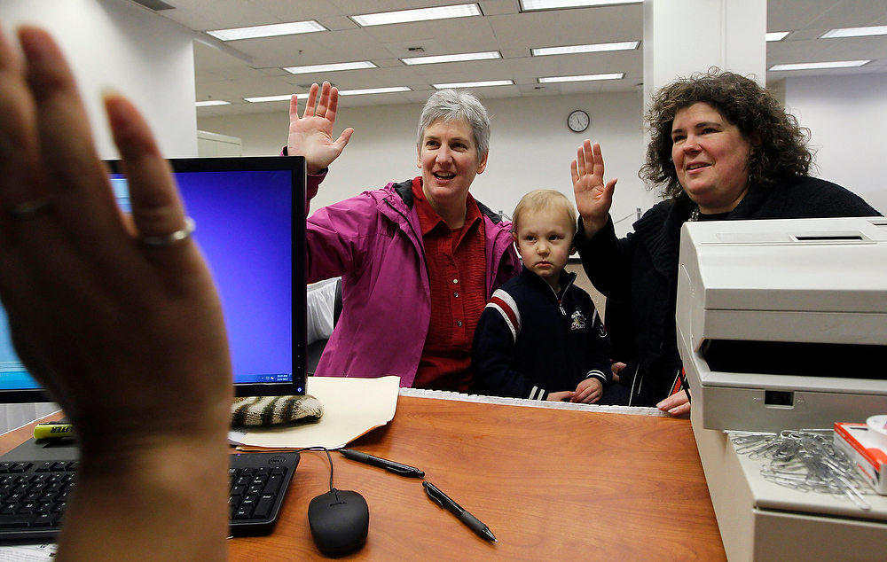 . Cynthia Riggin, left, and her partner Celeste Donville sit with their four-year-old son, who they declined to identify, as they raise their right hands to swear an affirmation as part of receiving a marriage license in King County Thursday, Dec. 6, 2012, in Seattle. Two by two, dozens of same-sex couples obtained their marriage licenses in Washington state Thursday, just hours after Gov. Chris Gregoire signed a voter-approved law legalizing gay marriage. King County, the state\'s biggest county, opened the doors to its auditor\'s office in Seattle just after midnight to start distributing marriage licenses. By noon, nearly 400 licenses had been issued in Seattle. Because the state has a three-day waiting period, the earliest that weddings can take place is Sunday. (AP Photo/Elaine Thompson)