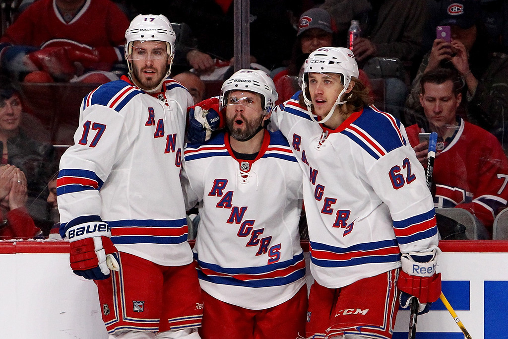 . MONTREAL, QC - MAY 17:  (C) Martin St. Louis #26 of the New York Rangers celebrates with teammates John Moore #17 and Carl Hagelin #62 after St. Louis scores a first period goal against the Montreal Canadiens in Game One of the Eastern Conference Finals of the 2014 NHL Stanley Cup Playoffs at the Bell Centre on May 17, 2014 in Montreal, Canada.  (Photo by Francois Laplante/Freestyle Photography/Getty Images)
