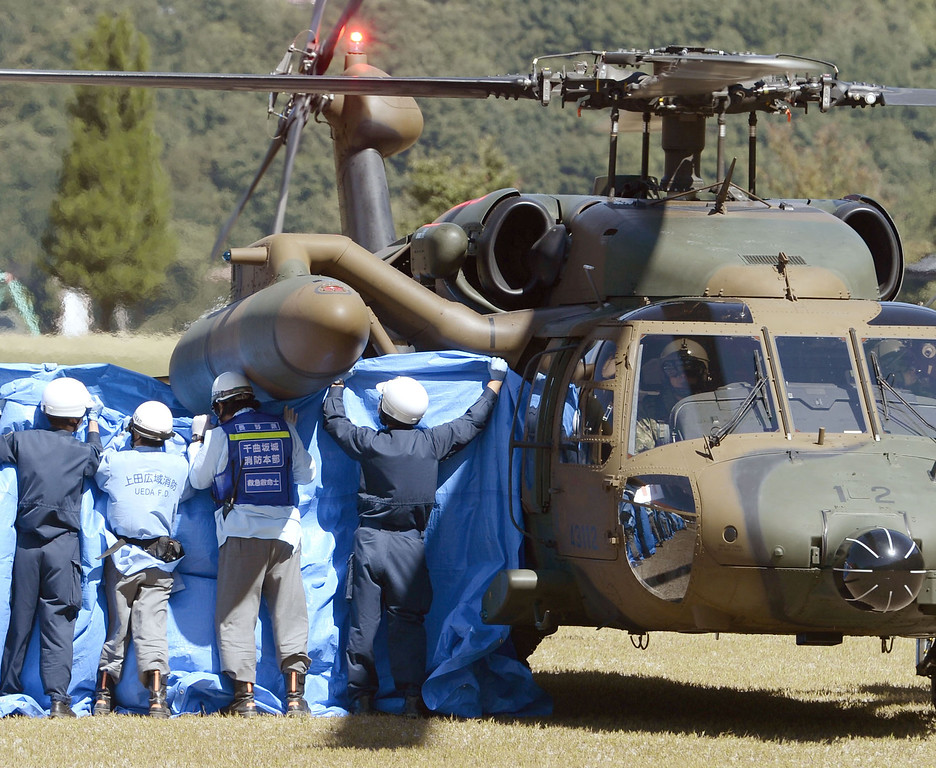 . Firefighters raise a blue sheet as a body of a hiker trapped in the mountaintop area during the eruption of Mount Ontake is airlifted by a Japan\'s Ground Self-Defense Force helicopter in Otaki in Nagano Prefecture, central Japan, Monday, Sept. 29, 2014. Japanese soldiers managed to bring down eight more bodies by helicopter from the ash-blanketed peak of a still-erupting volcano on Monday, before toxic gases and ash forced them to suspend the recovery effort in the early afternoon. (AP Photo/Kyodo News)