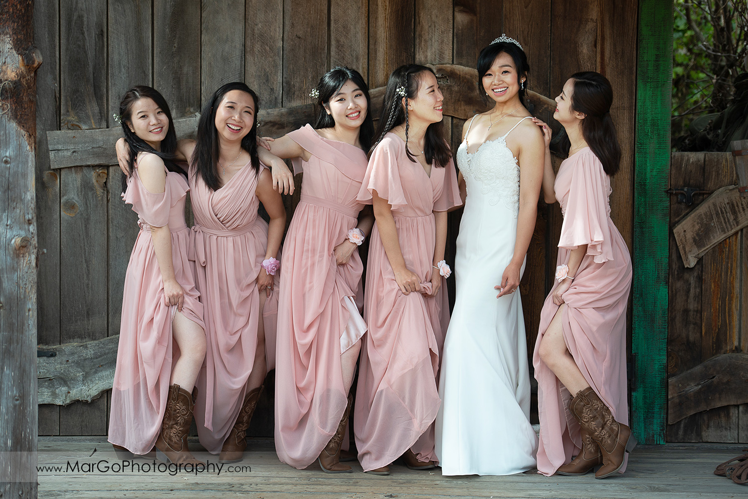 full body portrait of bride in white dress and bridesmaids in pink dresses at Long Branch Saloon & Farms in Half Moon Bay