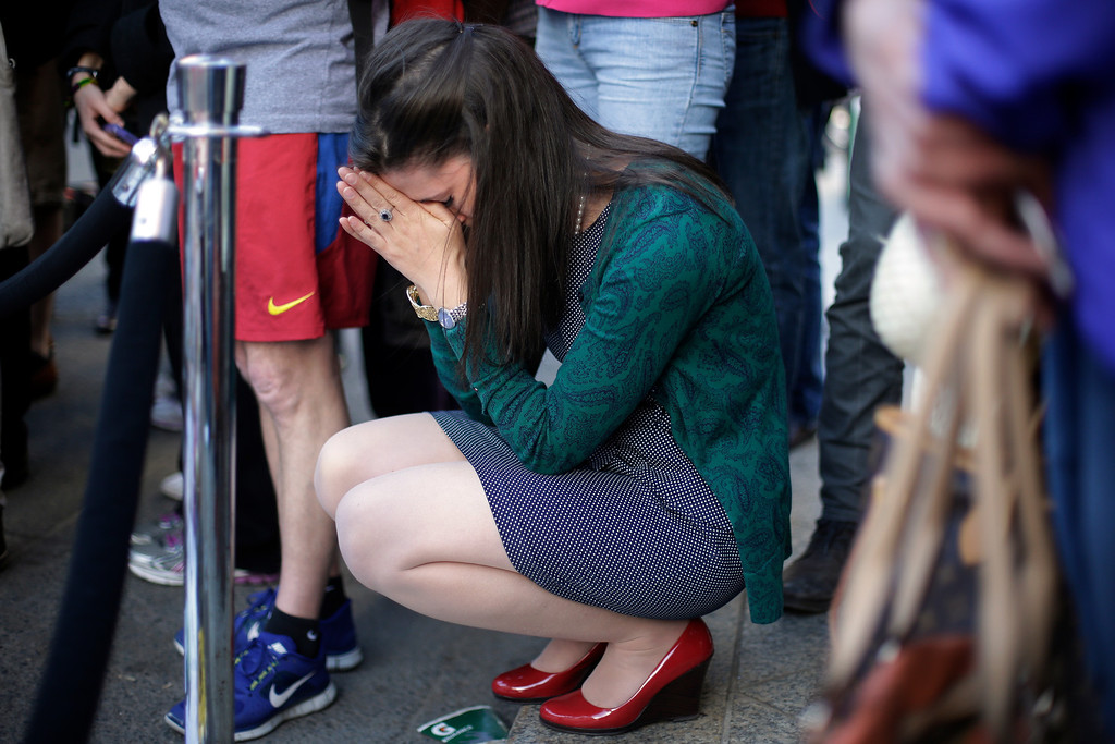 . Jennifer Krewalk attends a makeshift memorial on Boylston Street near the finish line of Monday\'s Boston Marathon explosions, which killed at least three and injured more than 140,  Wednesday, April 17, 2013, in Boston. (AP Photo/Matt Rourke)