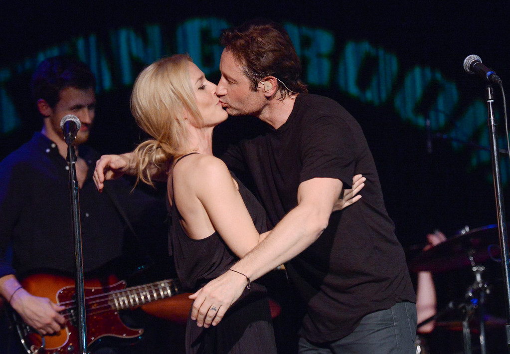 """. David Duchovny and actress Gillian Anderson kiss during their performance of Neil Young\'s \""""Helpless\"""" at The Cutting Room on Tuesday, May 12, 2015, in New York. Duchovny performed songs from his debut album \""""Hell Or Highwater.\"""" (Photo by Evan Agostini/Invision/AP)"""