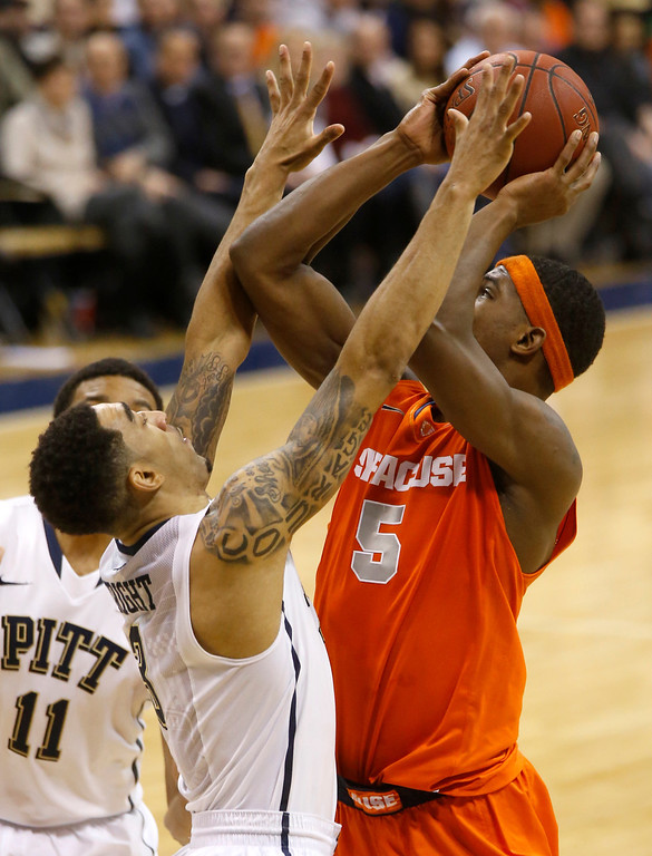 . Syracuse\'s C.J. Fair, right, shoots over Pittsburgh\'s Cameron Wright during the second half of an NCAA college basketball game on Wednesday, Feb. 12, 2014, in Pittsburgh. (AP Photo/Keith Srakocic)