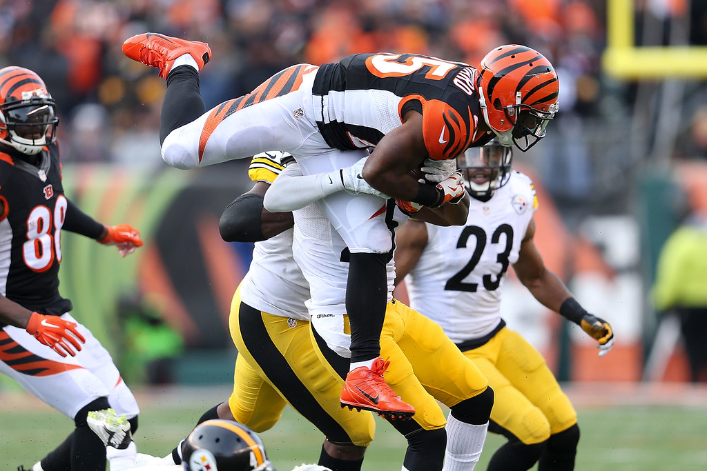 . CINCINNATI, OH - DECEMBER 7:  Giovani Bernard #25 of the Cincinnati Bengals is tackled by Brice McCain #25 of the Pittsburgh Steelers during the fourth quarter at Paul Brown Stadium on December 7, 2014 in Cincinnati, Ohio. Pittsburgh defeated Cincinnati 42-21. (Photo by Andy Lyons/Getty Images)