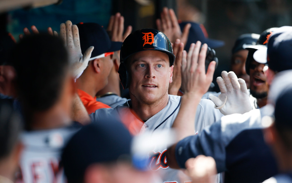 . Detroit Tigers\' Jim Adduci celebrates in the dugout with teammates after hitting a three run home run off Cleveland Indians\' Shane Bieber during the fifth inning of a baseball game, Sunday, Sept. 16, 2018, in Cleveland. (AP Photo/Ron Schwane)