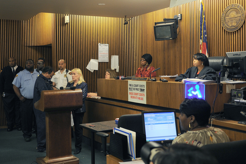 Description of . Ariel Castro(podium-L) at Cleveland Municipal Court in front of judge Lauren Moore(R)in May 9, 2013 in Cleveland, Ohio. Castro appeared in court Thursday to faces charges that he kidnapped and raped three young women and held them in his home for a decade. The 52-year-old from Cleveland, Ohio did not enter a plea and stood with his head bowed while the court set a large bond of two million dollars per case, effectively ensuring that he will remain in detention. Ariel Castro was presented to the court by public defender Kathleen DeMetz(podium-R), who said he was