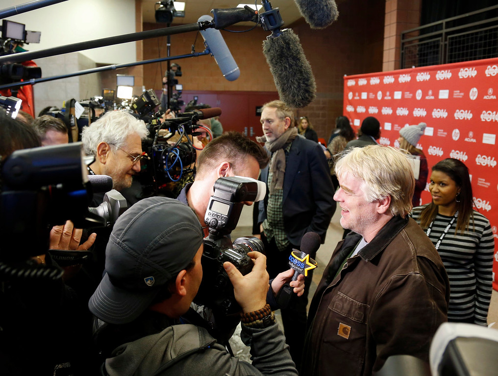 """. Cast member Philip Seymour Hoffman, right, and Director Anton Corbijn, rear, are interviewed at the premiere of the film \""""A Most Wanted Man\"""" during the 2014 Sundance Film Festival, on Sunday, Jan. 19, 2014, in Park City, Utah. (Photo by Danny Moloshok/Invision/AP)"""