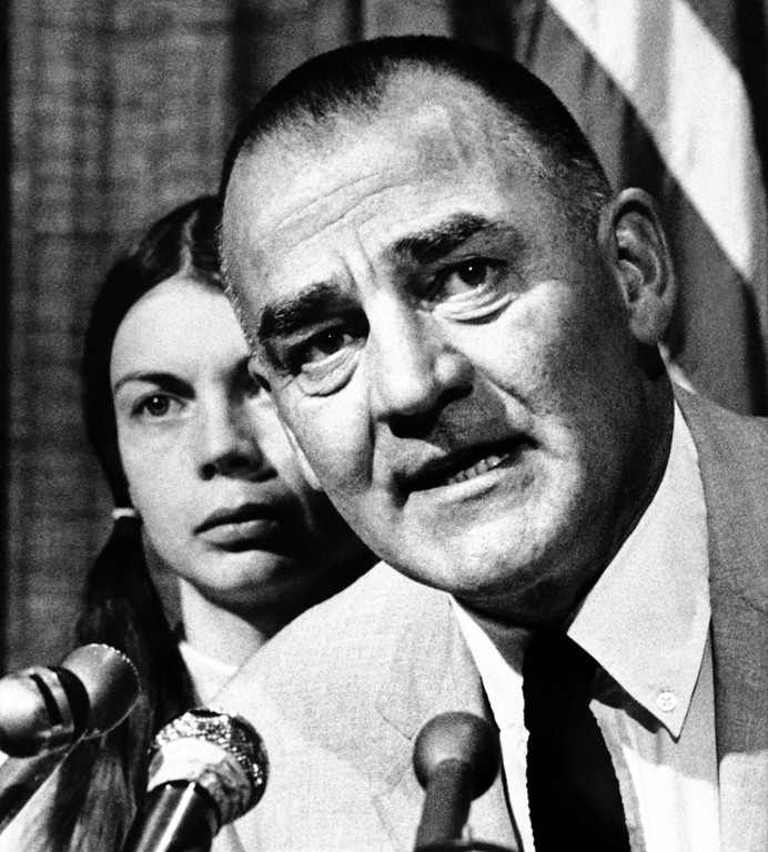 . Dr. L.S. Wolfe, an Emmaus, Pa., anesthesiologist, tells a Los Angeles news conference, Thursday, May 30, 1974, he wants an investigation into the gun battle and fire that left his son, William, and five other SLA members dead. Behind him is his wife, Sharon. (AP Photo/Jeff Robbins)